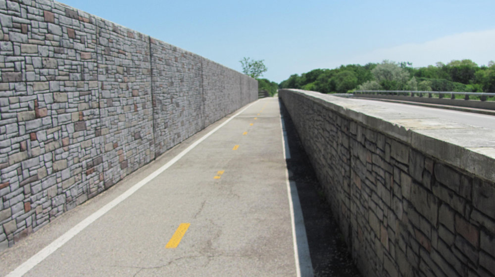 An existing bridge that had damage from salt.  Powerwashed exiting walls, patched all holes, then used Brickforms Triple Seven bond coat, used Brickforms Vertical mix, used Brickforms color and Solvent Based Gem-Seal.
