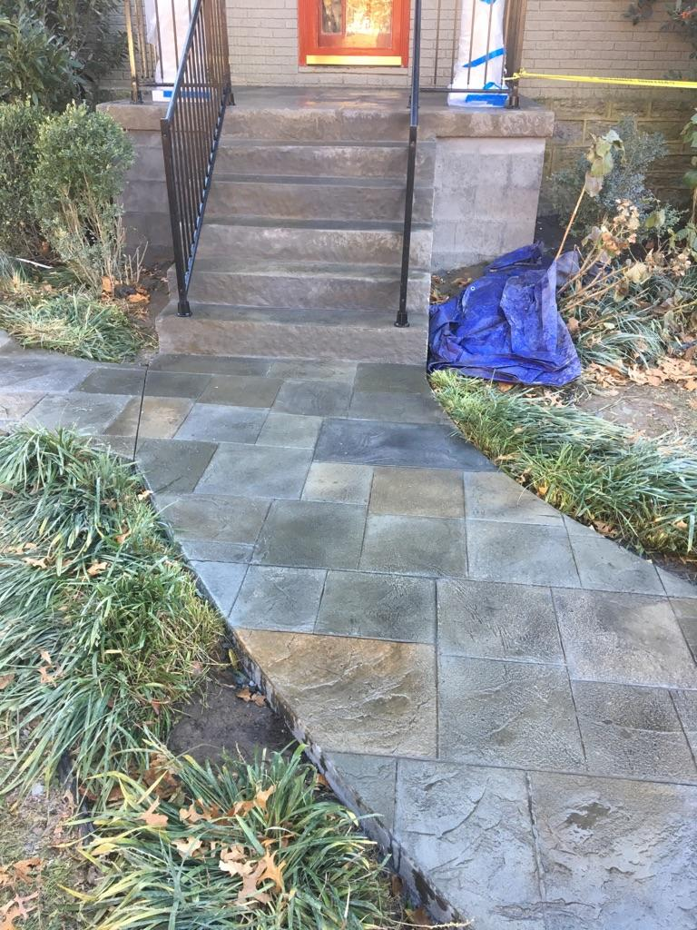 A picture of a job in progress this fall; the customer and our team collaborated to create a unique porch and walkway. Brickforms large ashlar slate stamps were use, as well as, slate step liners. A variety of Brickform color hardener and release powdered colors were used, followed by a dark grey Antique-It. Individual stones were colored and Gem Seal coated it all! This project was a highlight for the neighborhood!