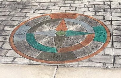 This expansive stamped driveway utilized the UK Cobblestone stamp pattern with Light Gray color highlighted by the Antique process.  The Compass medallion was hand painted with Smokey Blue and Desert Tan.