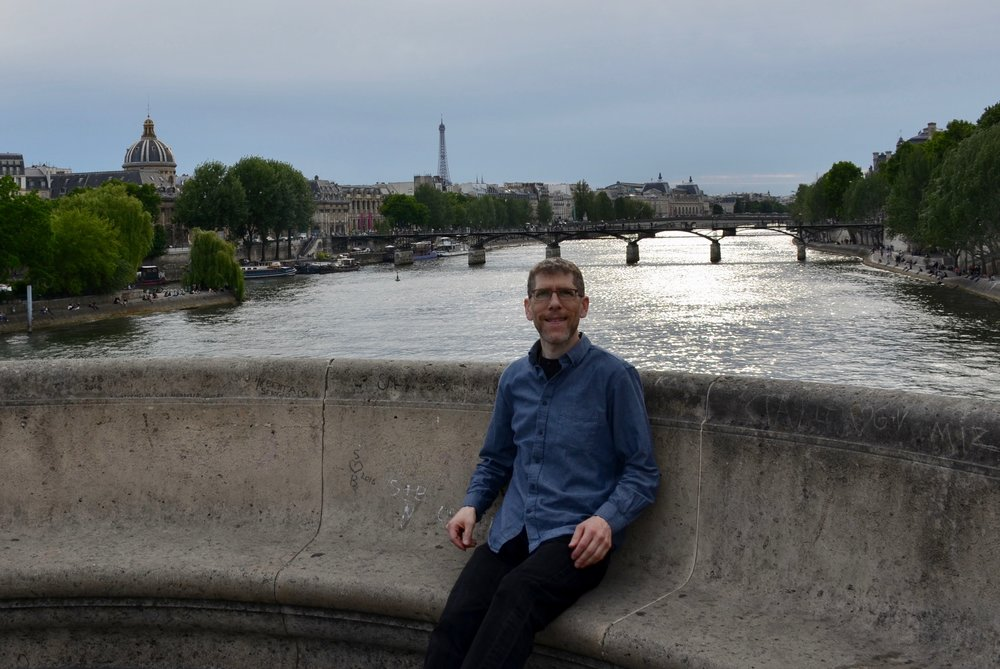 Chris Porter standing alongside the Seine River - Boston Organ Studio