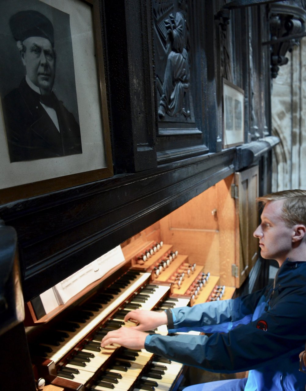 Jon Ortloff, organ builder, performing Widor. under a photo of Aristide Cavaillé-Coll in Rouen