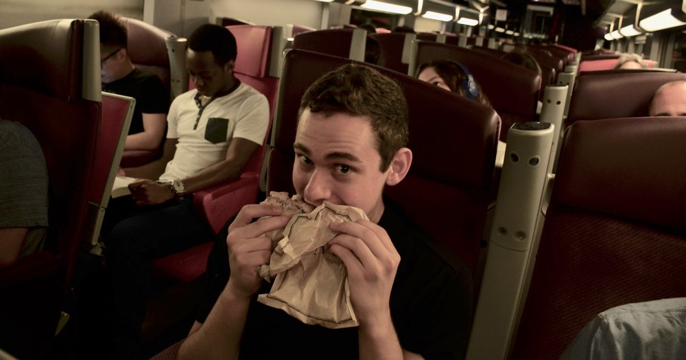 David messily eats his sandwich on the train, only dropping a few pieces of food on the floor.