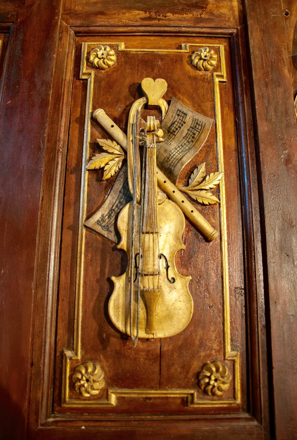 Detail of the case work -- an actual violin affixed to the organ case in St Felix-Lauragais