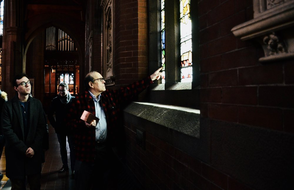 Thomas Murray pointing out details in the stained glass.
