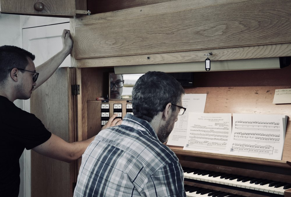 Chris Porter plays the organ in Göteborg Cathedral, while Corey De Tar looks on.