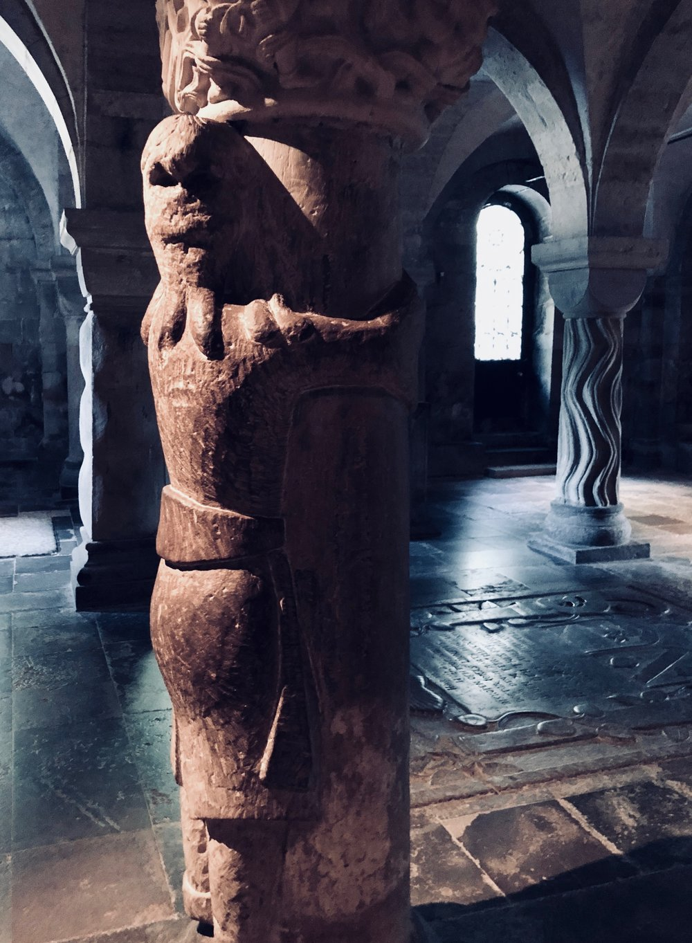 Finn, turned into stone, holding onto one of the stone columns in the crypt of Lund Cathedral.