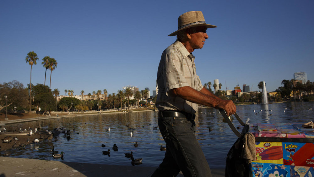 Patrick T. Fallon / For The Times  Victor Montes, 72, pushes his ice cream cart around the lake at MacAthur park at sunset.