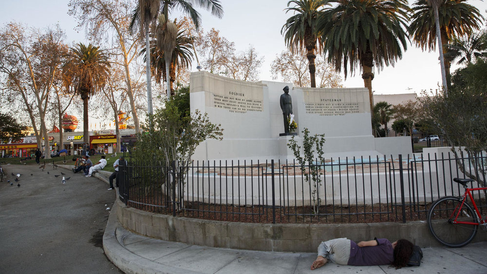 Patrick T. Fallon / For The Times  A barefoot woman sleeps beneath a memorial of Gen. Douglas MacArthur at MacArthur Park in Los Angeles' Westlake neighborhood.