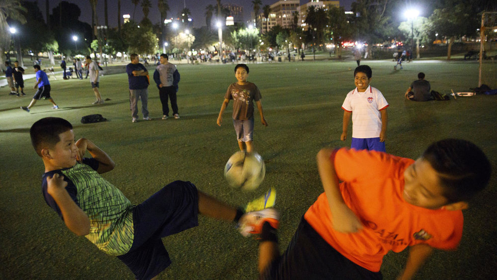 Patrick T. Fallon / For The Times  Dylan Hernandez, 9, left, Christian Juarez, 11, Angel Tistoj, 10, and David Chaj, 11, practice their soccer skills after sunset at MacArthur Park.