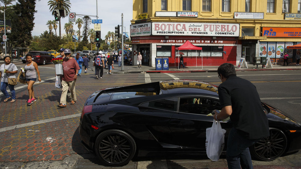 Patrick T. Fallon / For The Times  Pedestrians cross 7th Street at Alvarado Street next to MacArthur Park as a Lamborhini driver waiting for carry-out from Langer's Deli idles on Oct. 7.