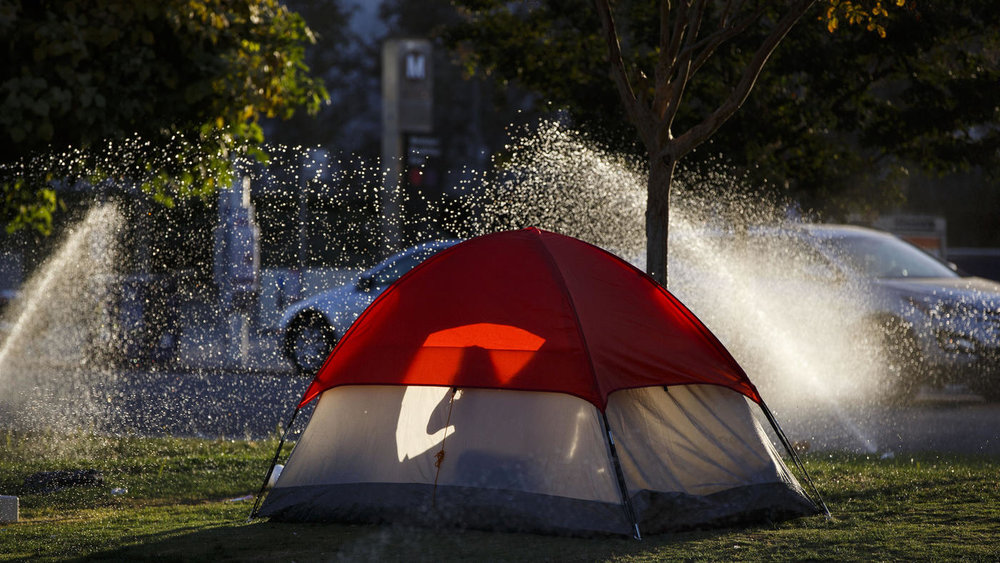 Patrick T. Fallon / For The Times  A homeless woman sits in her tent as sprinklers water the grass at MacArthur Park.
