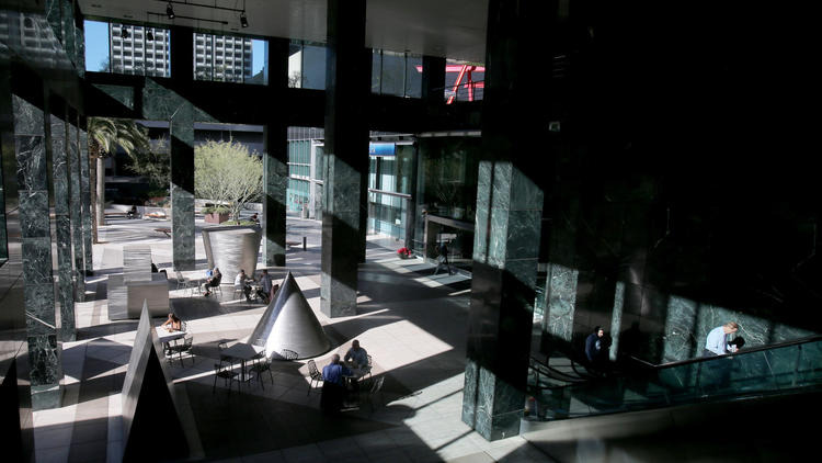 People meet, dine and walk around the shadows and sculptures in the covered plaza outside the Citigroup Center. (Luis Sinco / Los Angeles Times)