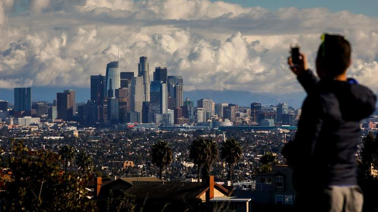After dropping a friend at LAX airport, Mike Che, from West Hollywood, stopped at Kenneth Hahn State Recreation Area to take in the skyline of downtown Los Angeles, CA, following a winter storm, Christmas Eve morning. (Jay L. Clendenin / Los Angeles Times)