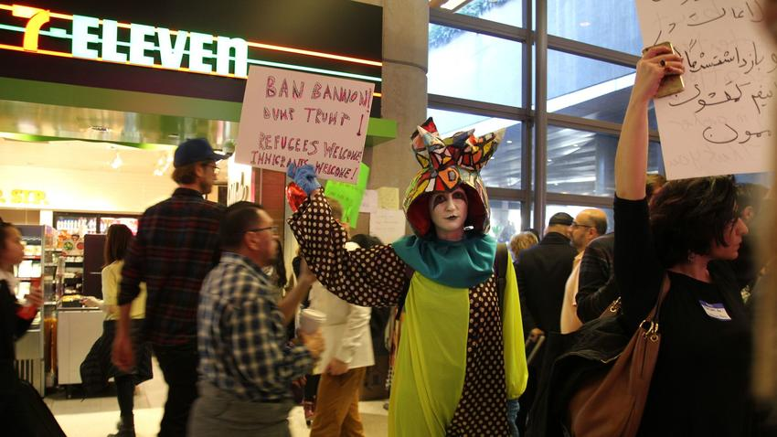Artist Rachel Mason, dressed as her character FutureClown, stands among protestors at the arrivals gate at Tom Bradley International Airport. (Carolina A. Miranda / Los Angeles Times)