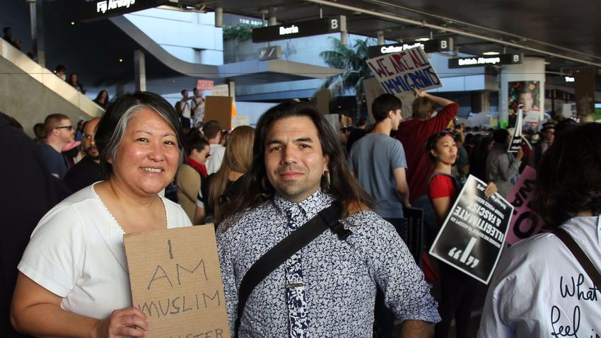 Arts writer Carol Cheh and artist and administrator Marshall Astor protest Trump's travel ban at Tom Bradley International Terminal at LAX. (Carolina A. Miranda / Los Angeles Times)