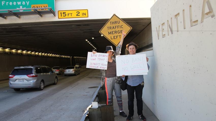 Artists Rachel Mason, left, and Ilona Berger make their way to the protest at LAX. (Carolina A. Miranda / Los Angeles Times)