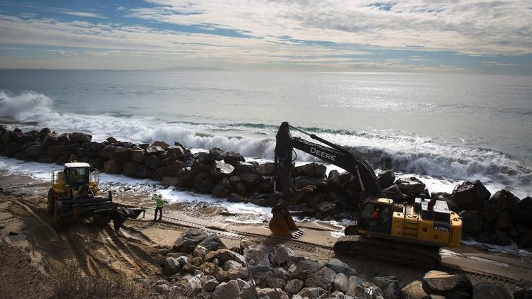 Caltrans contractor Nordic Industries works on constructing a rock barrier against erosion from tidal forces near Las Tunas Beach along Pacific Coast Highway in Malibu. (Brian van der Brug / Los Angeles Times)