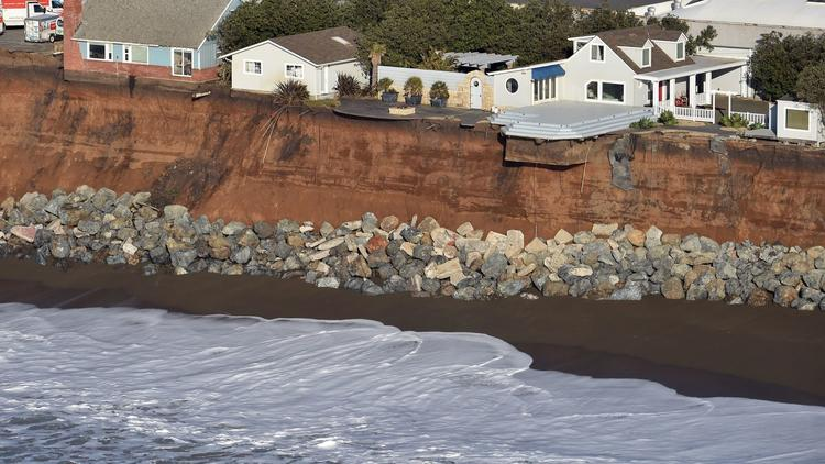 Houses hang on the edge of an eroding cliff in Pacifica, Calif. (Josh Edelson / AFP-Getty Images)