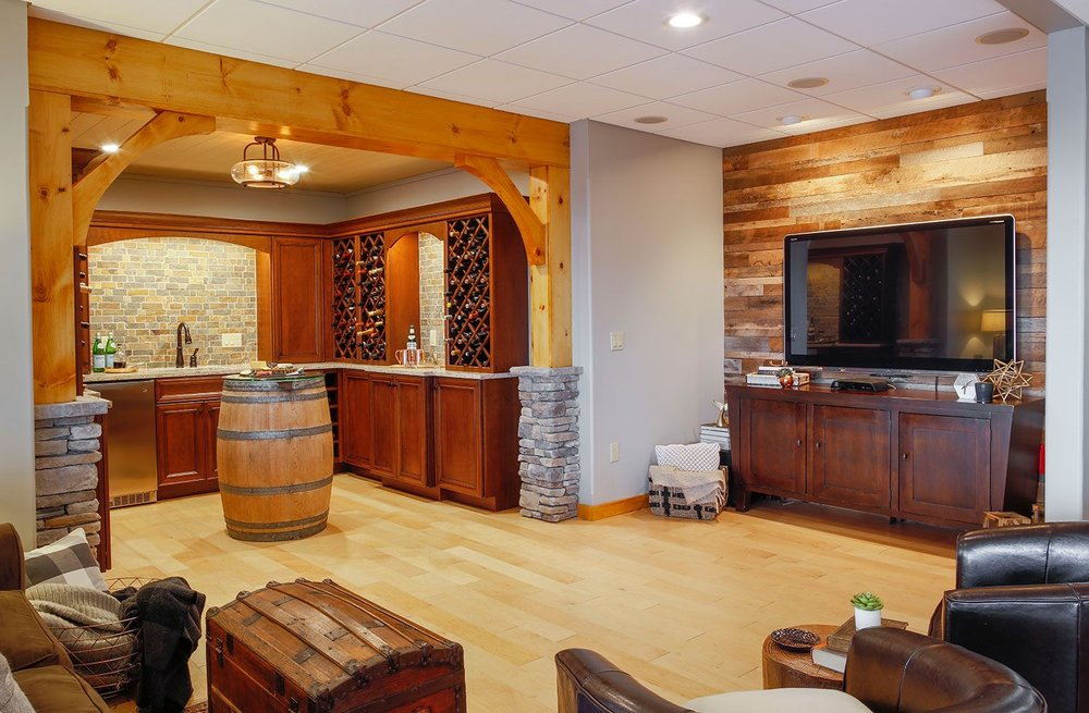 Designer touches - reclaimed wood wall behind TV, stone-wrapped columns, wine storage