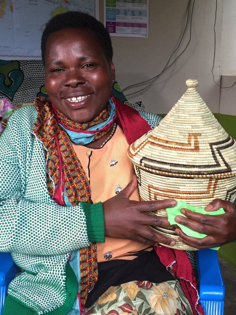 Lovinah, ACT Weaver Quality Manager, is holding one of her own exquisite baskets.