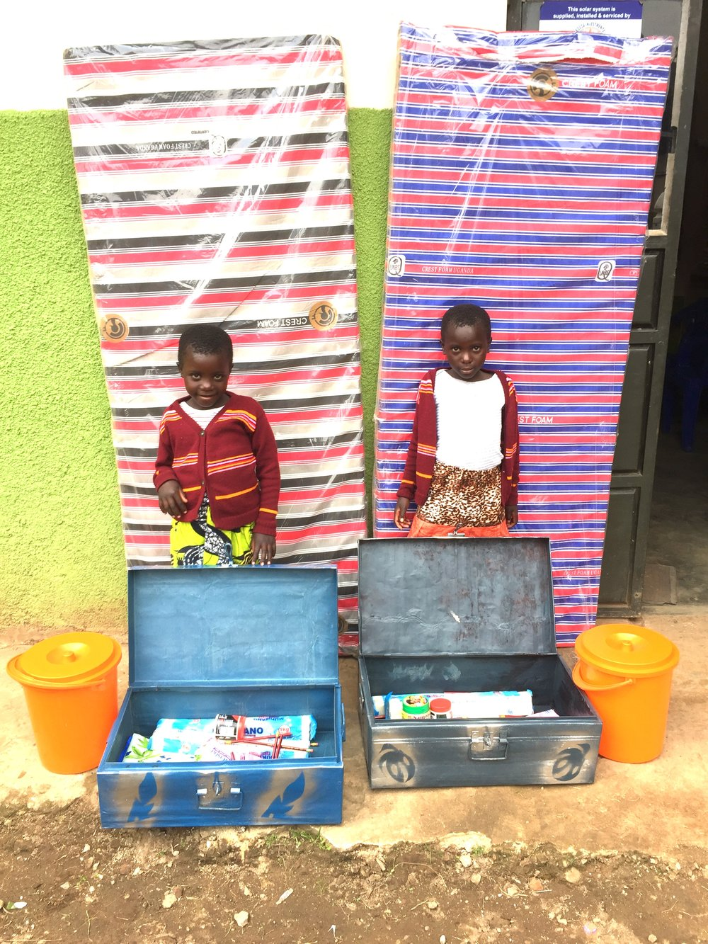 Two sweet girls who are twin sisters! They are sponsored for the first time and this photo shows all the supplies that the sponsorship purchases for their first year in school. Their mattresses are behind them. They will be attending Uganda Martyr's Primary School.