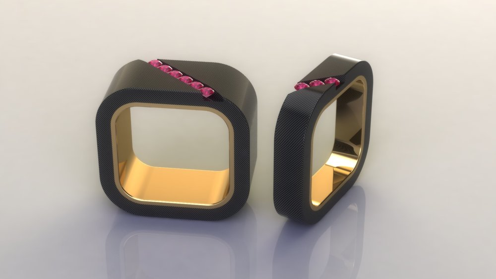 Mens wedding bands in black carbon fiber and 18k yellow gold , and just a few pink sapphires for a splash of color.