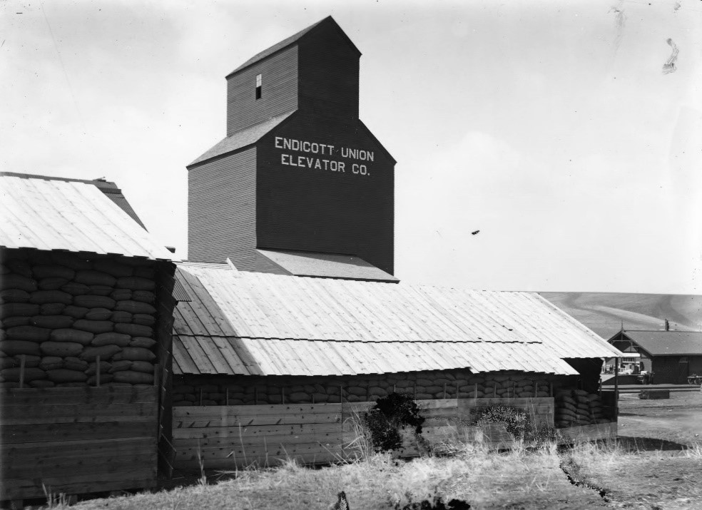 Endicott Union Elevator Company and Flathouse Railroad Grain Sack Storage (c. 1920);   R. R. Hutchison Photograph Collection, WSU Terrell/Allen Library, Pullman