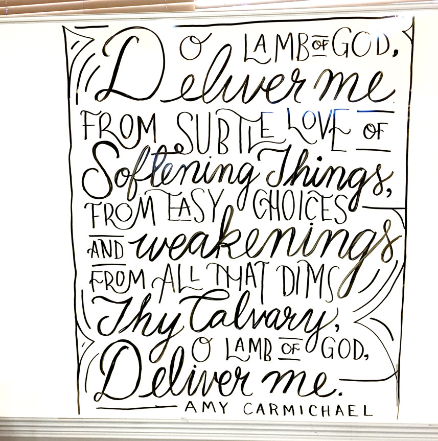 """""""O Lamb of God, deliver me, from subtle love of softening things, from easy choices and weakening, from all that dims Thy Calvary, O Lamb of God, deliver me."""" —Amy Carmichael //This hand-lettered calligraphy whiteboard design was made by Sarah Mikucki of Doorpost Designs for a women's ministry event at Grace Christian Fellowship Church in Spokane, WA."""