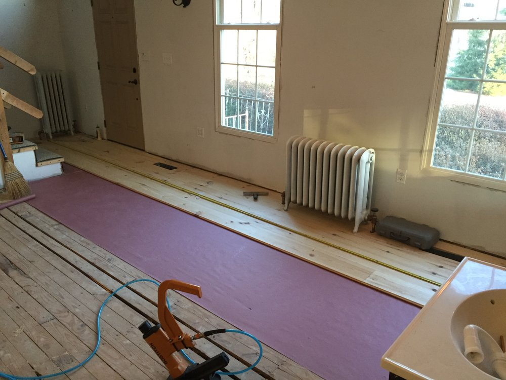 "After the old floors had been removed, new 8"" wide red pine floors were installed."