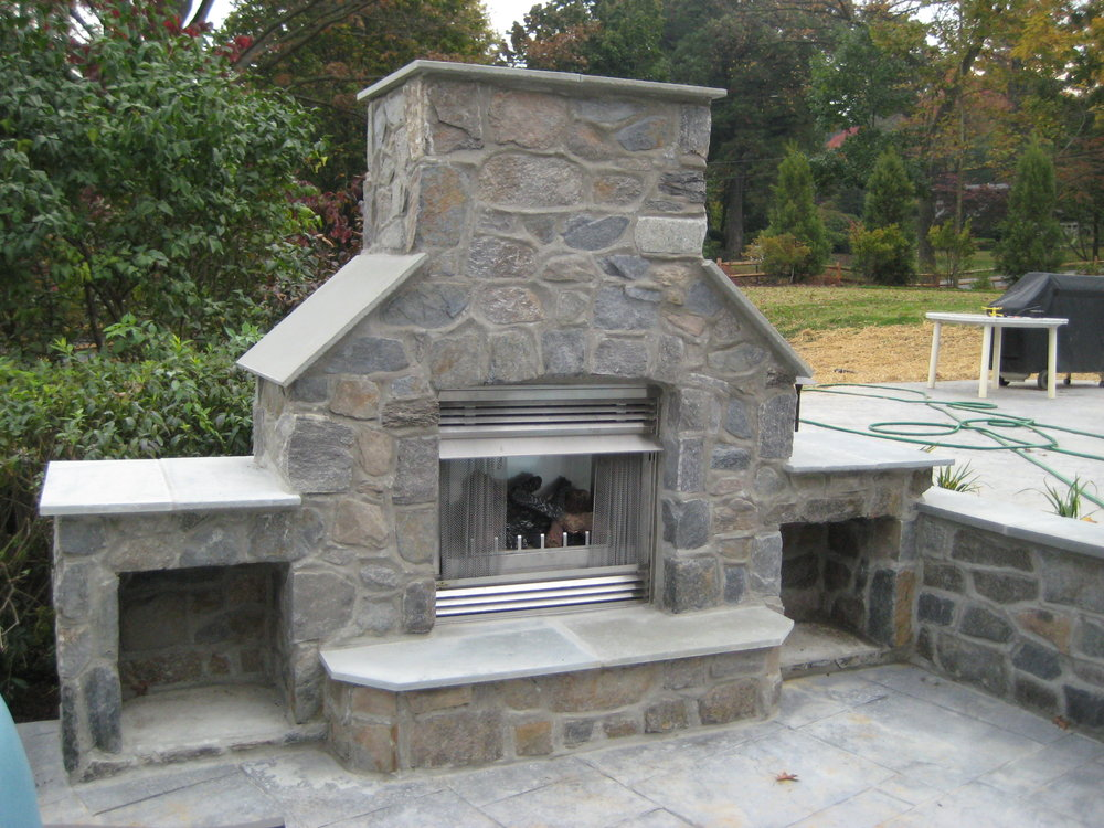 Here, the gas fireplace unit has been installed and stone has been applied to match the garage and house.