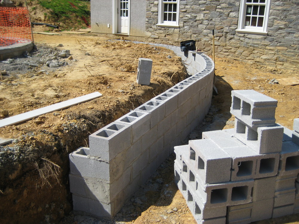 The blockwork for the retaining wall is in place, which separates the lower patio from upper patio/pool deck.