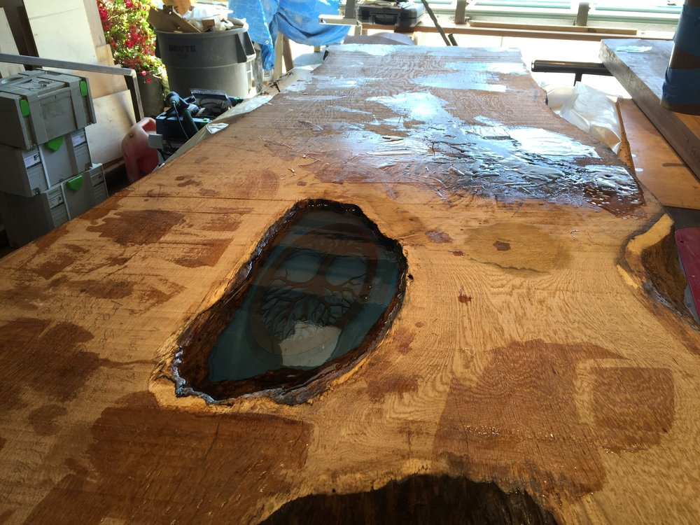 The client had a tree of life emblem she wanted embedded in the hole, so after I closed the bottom off with plexiglass, I installed the emblem in the middle of multiple layer of crystal clear epoxy.