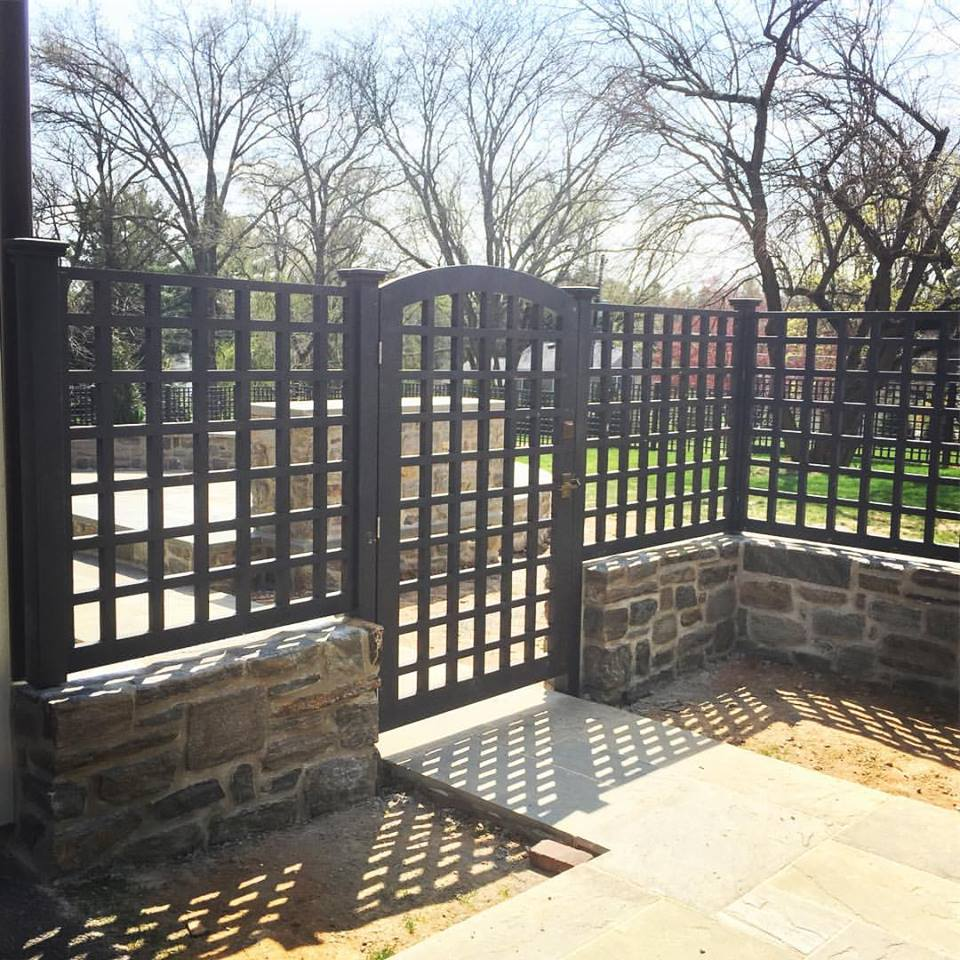 An arched gate provides the main entry area to the back yard. There is another single gate on the far side of the property, along with two sets of double gates to allow mowers and other equipment into the property. All the latches and hardware were custom made by Rocky Mountain Hardware.