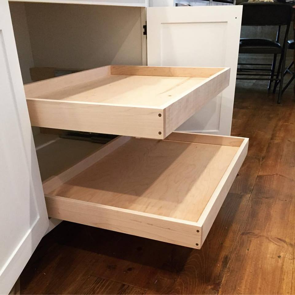 These are the pull-out shelves my daughter was sitting on in the last picture. Typically I make my drawers with dovetail joinery, but in this case I wanted to do something different, so I made them from solid maple with a housed rabbet joint in each corner, and then pinned that joint with walnut dowels. These pull-out shelves hold all my cast iron pots and pans and function perfectly under that heavy load.