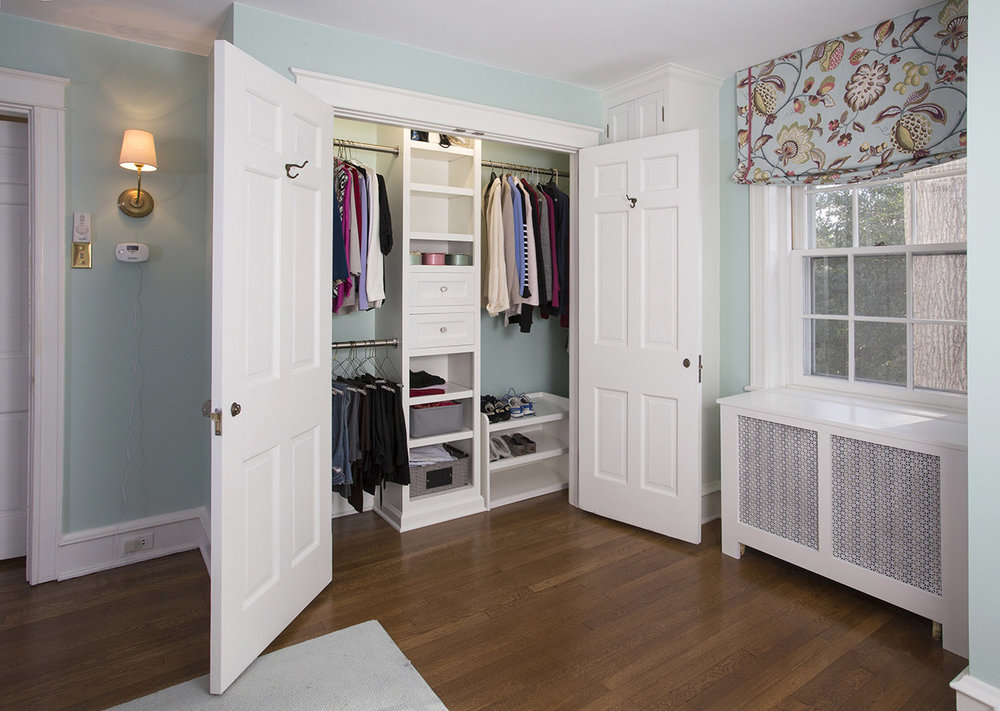 The newly enlarged closet opens to reveal multiple hanger rods, a central built-in with inset drawers and adjustable shelving, and a custom shoe rack for additional storage.