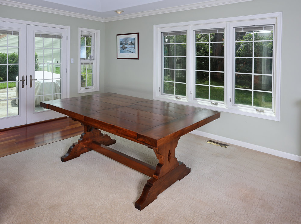 "This farmhouse table was commissioned by a client looking for a large sturdy table to use for family gatherings. I designed a traditional trestle table with large sturdy legs to match the 2-1/2"" thick maple top."