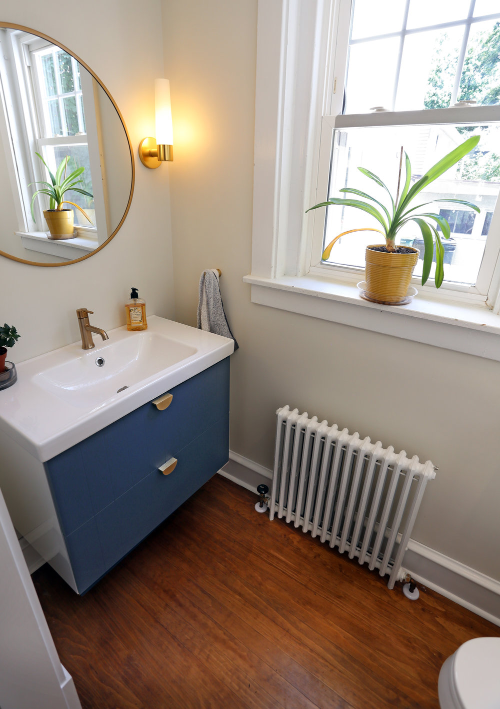 In the original mudroom there had been a small water closet. Part of the renovation included expanding it into a proper powder room. This powder room got new fixtures, cabinetry, lighting, flooring, and a slimline radiator.