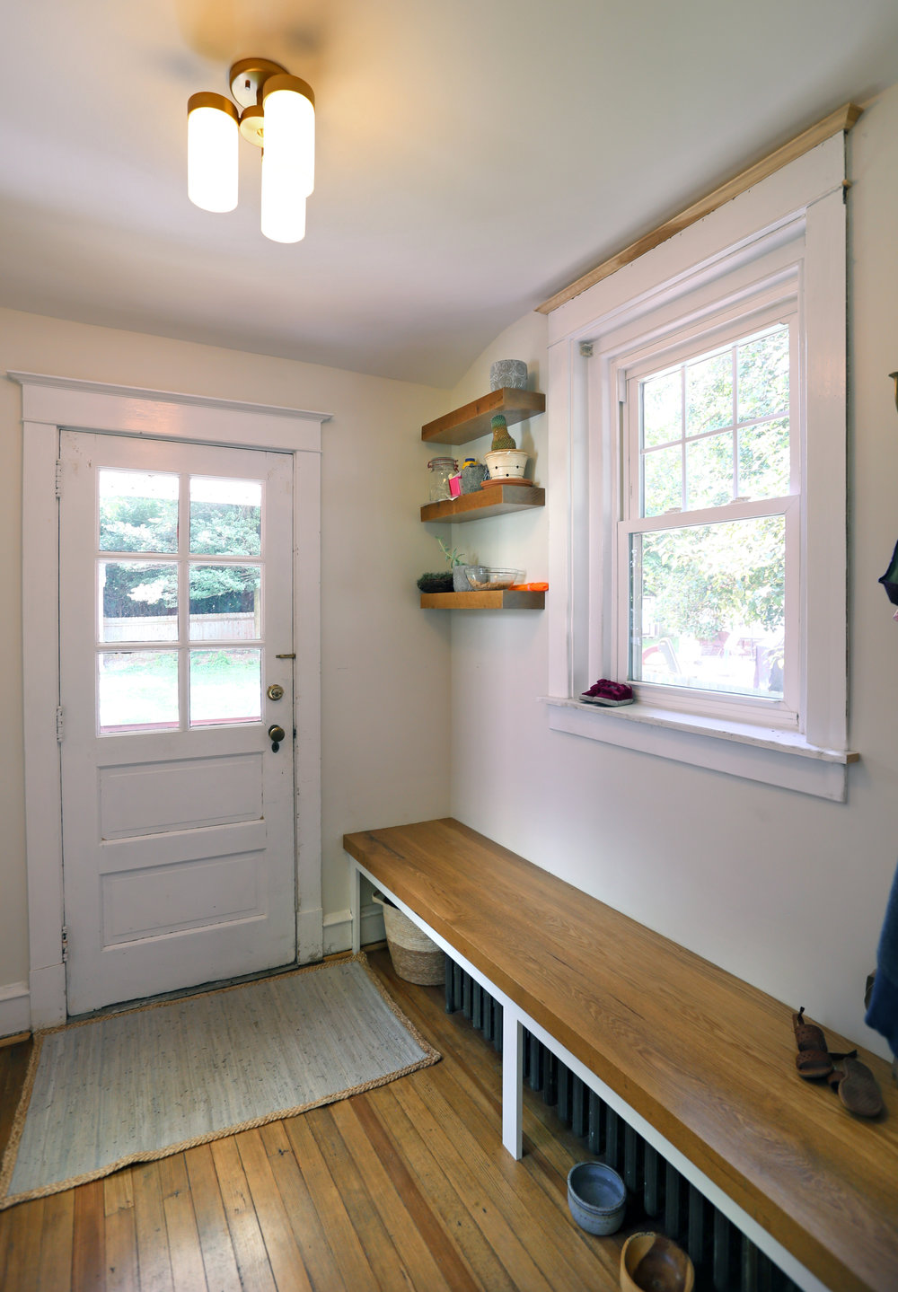 The remainder of the mudroom received a new lowboy radiator, rough-sawn floating maple shelves, refinished floors, and a new mudroom bench with a solid maple top.