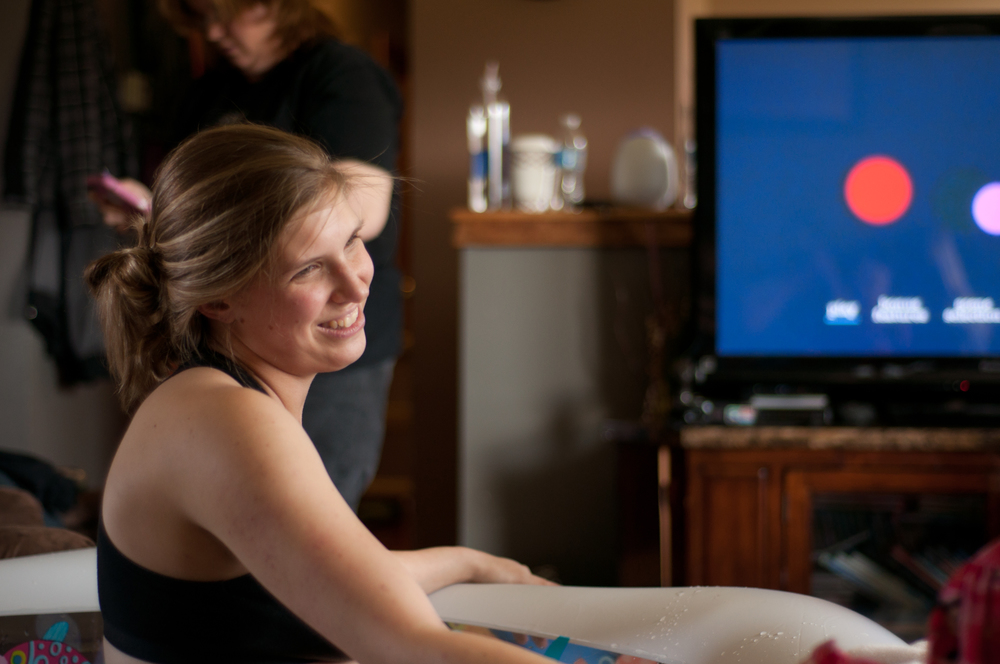 Laboring mother laughs during a break in contractions at photographed home birth in Peoria IL area.