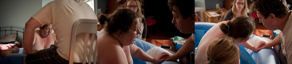 Mother helps guide out her newborn during a photographed home birth in Bloomington-Peoria IL area.