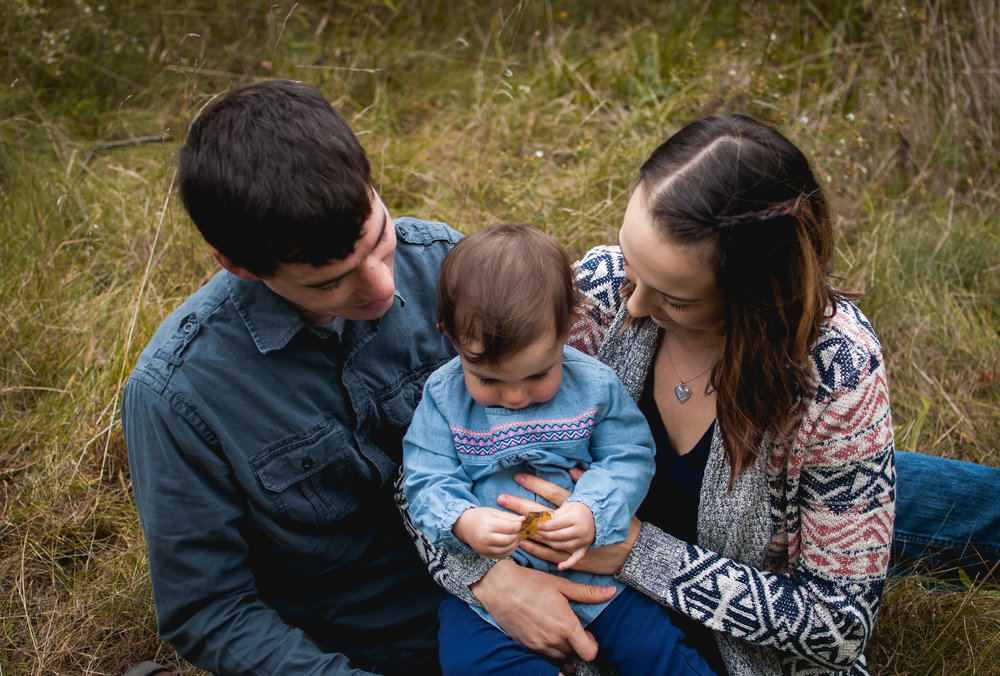 Birth, newborn, baby and family photographer Brittney Hogue captures child sitting with parents during a family session in the Pekin-Peoria Illinois area