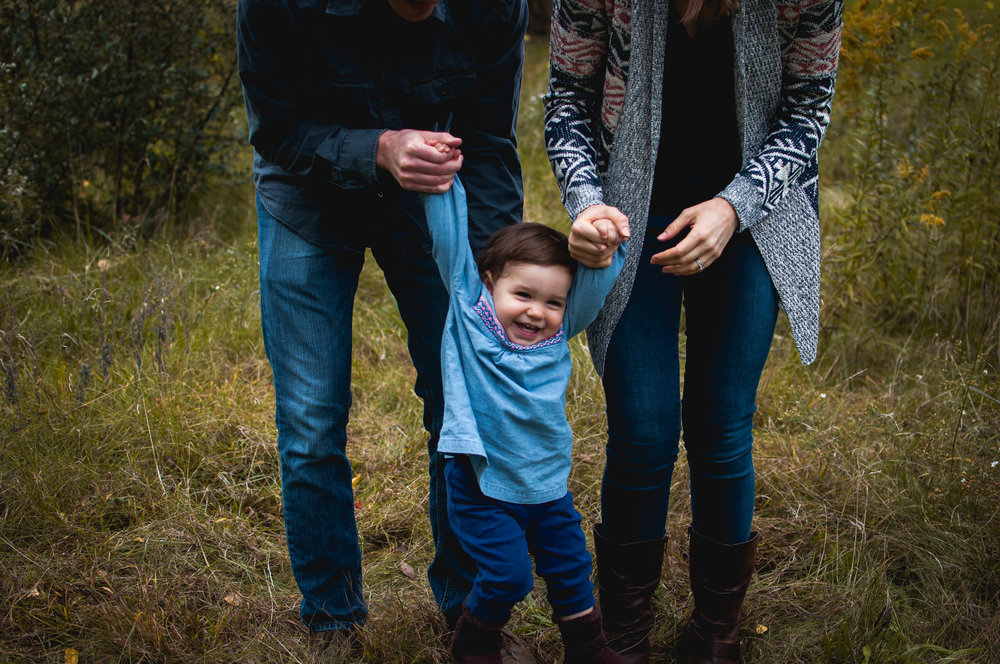 Child laughs with parents while photographed by birth, newborn, and family photographer Brittney Hogue.