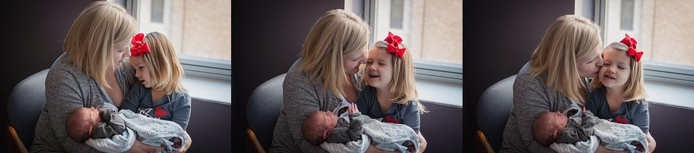 Big sister laughs with mom while meeting baby sister during hospital newborn session at OSF St Francis in Peoria, IL.
