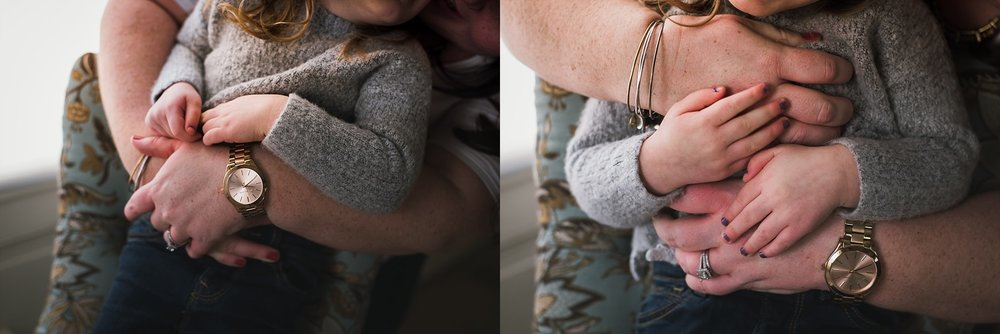 Photographer features mother's hands wrapped around child.