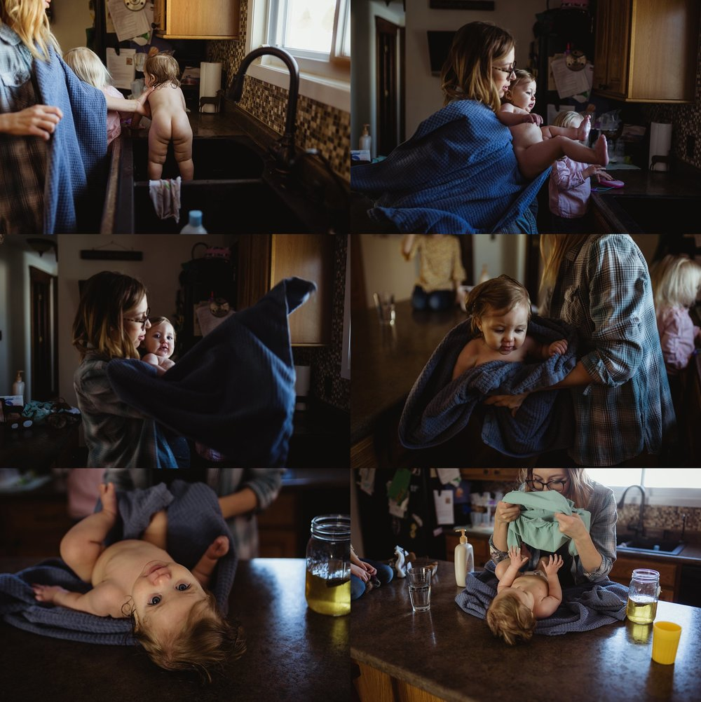 Mom lifts baby from sink after bath. Brittney Hogue photographs families and newborns in the Peoria IL area/