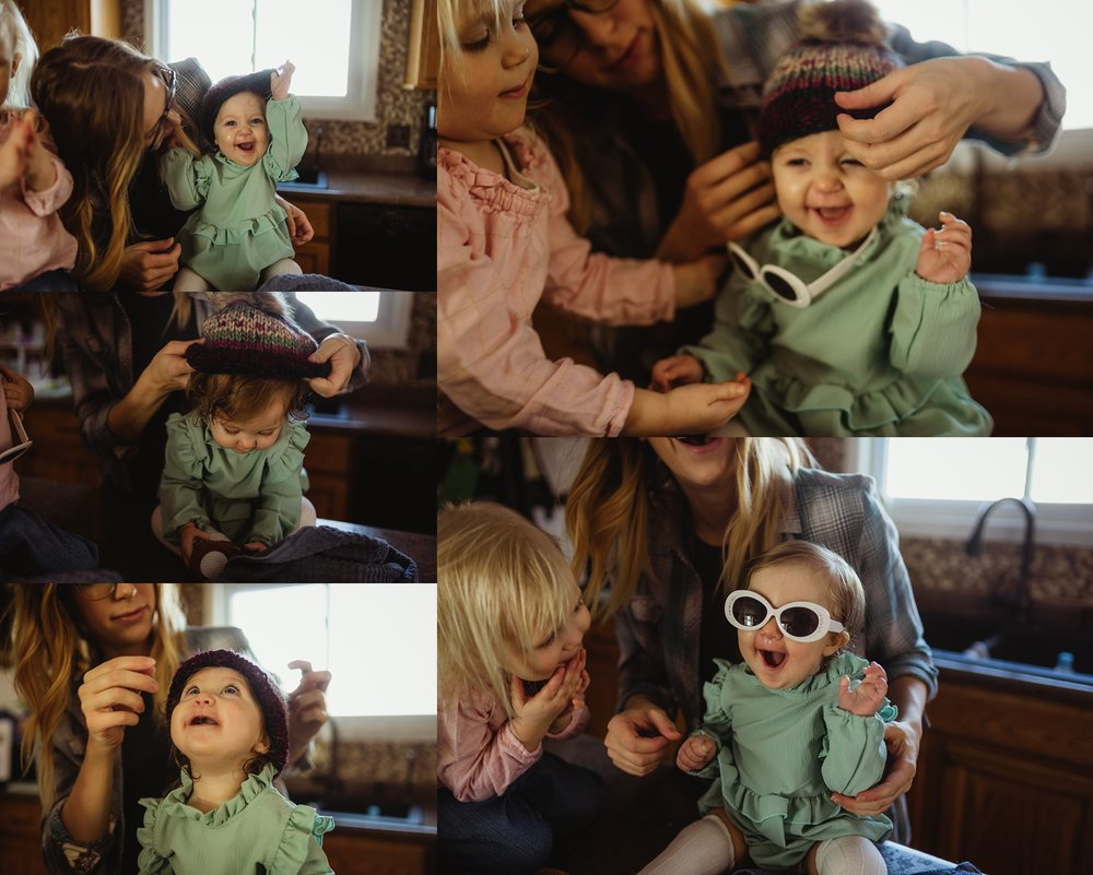 Baby wears sunglasses while laughing during family photo session.