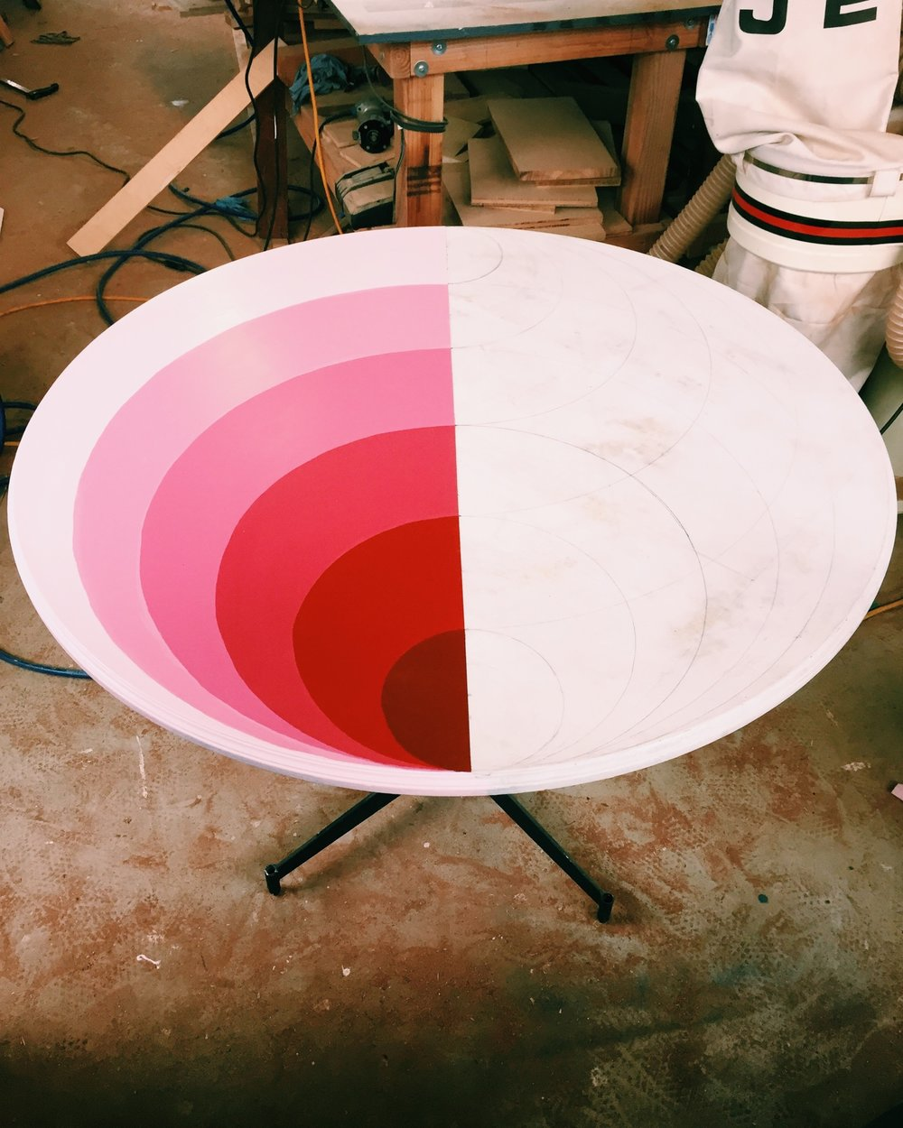 Kristina was working on this awesome circular table that we've reclaimed. Here is the first half of the table painted. The other half will be different gradients of blue.