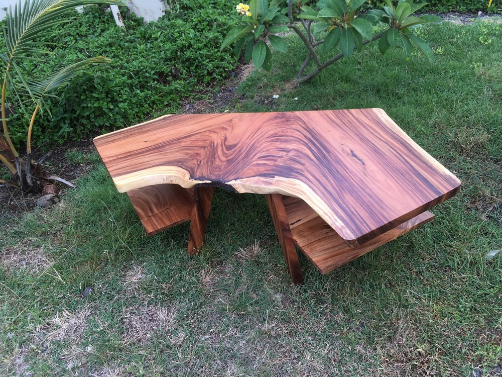 Monkeypod coffee table with a custom base designed to fit the strange shape and keep the table stable. Shelves added for storage underneath!