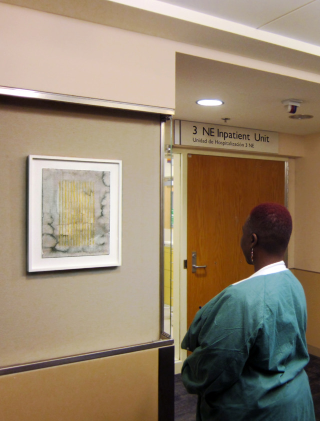 A woman views a painting by Mary Early.