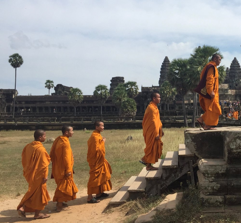 "Monks strolling the grounds outside Angkor Wat, which means ""Capital Temple"" in Khmer."